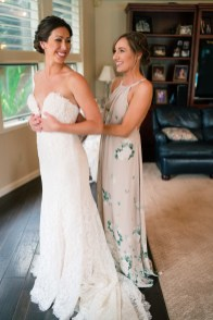 Bridesmaid helping bride put on wedding dress