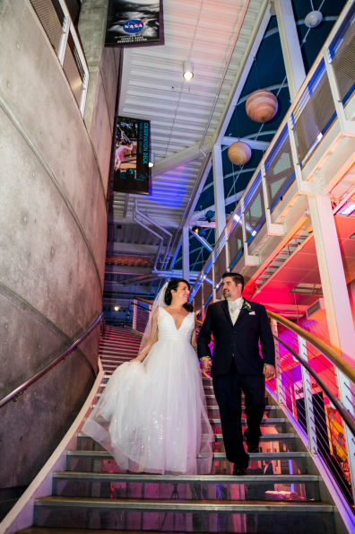 Bride and groom walking down illuminated staircase