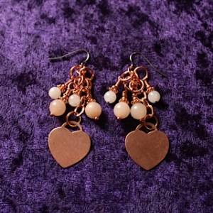 Photo of copper heart earrings with rose quartz beads.