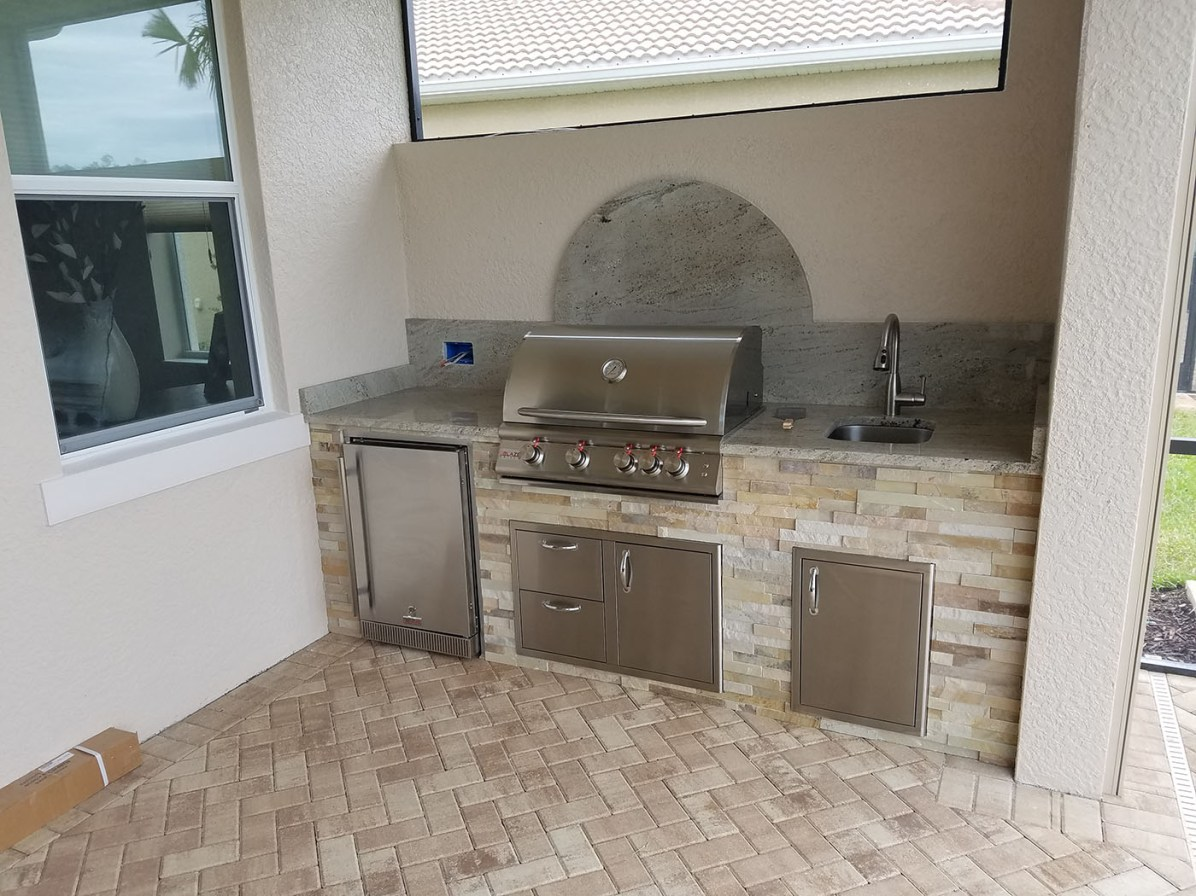 This custom barbecue island by Elegant Outdoor Kitchens has a beautiful Mint Sandstone veneer finish and we used Millennium Granite for the Countertop finish