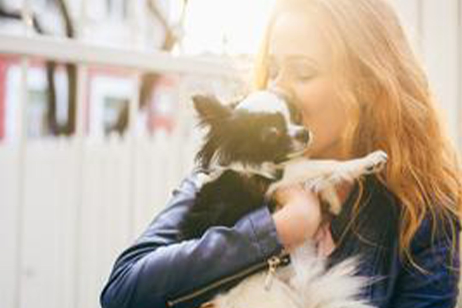 A young lady wearing a blue jacket holding and kissing a small black and white dog.