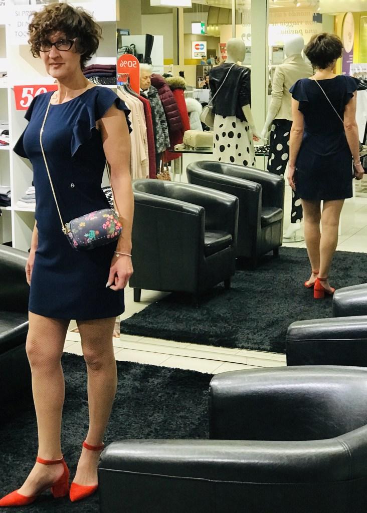 Modella indossa abito a tubino, volant sulle maniche, di Nero Giardini, borsa a tracolla di Liu Jo e scarpe rosse di Nero Giardini