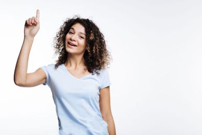 88562848 - upbeat curly woman pointing up with her finger