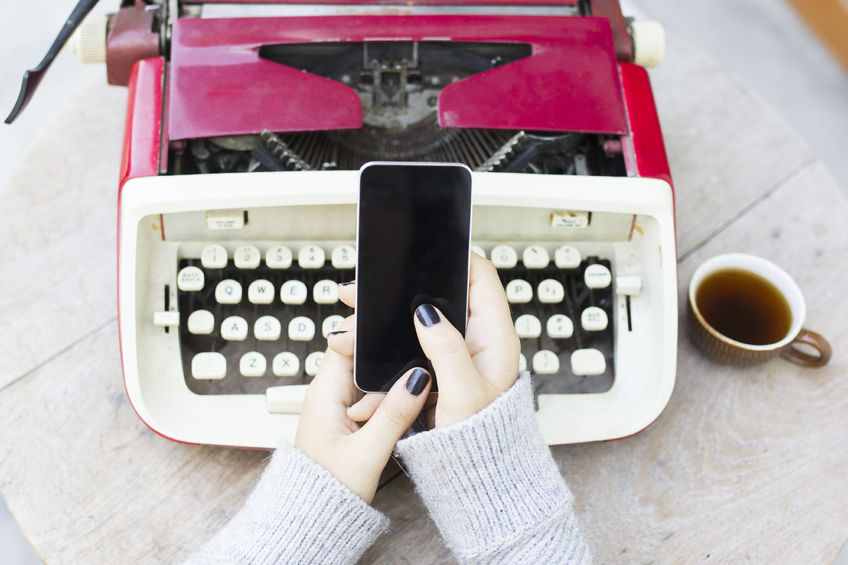 44093570 - girl with cell phone and typewriter