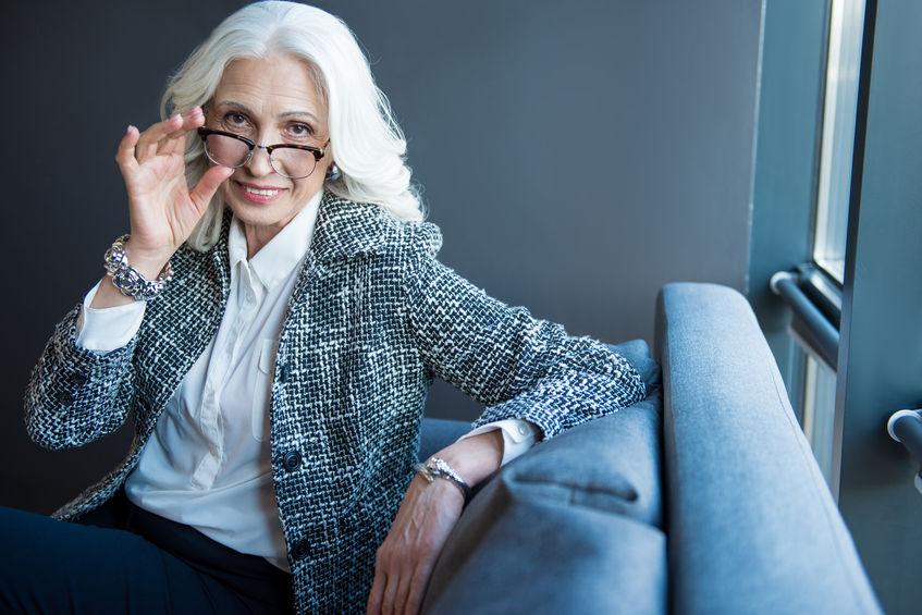 89053207 - positive senior elegant businesswoman is sitting on sofa