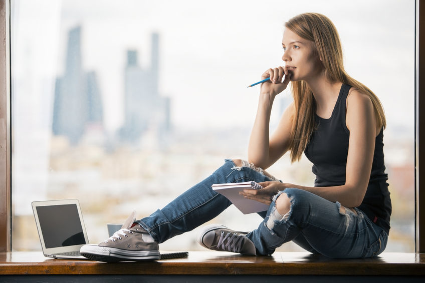 56779373 - thoughtful young woman with notepad in hand sitting on windowsill with blank laptop screen. blurry city view in the background. mock up