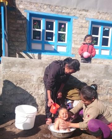 kid bathing in everest trek village