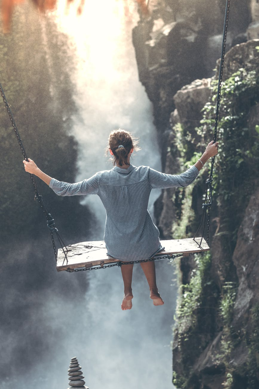 Woman traveler on a swing over a waterfall