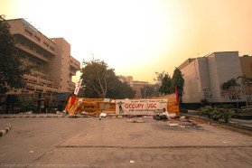 """The immediate sight of the yellow police barricades adorned with the """"main banner"""" is unmistakable and unmissable. This relatively humble physical core seems not the least intimidated by the towering structures of administrative and public buildings that surround it. Beyond these barricades, rest the hallowed precincts of the University Grants Commission (UGC)."""