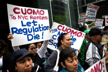 FILE--In this May 6, 2015 file photo, protesters hold signs during a demonstration in front of New York Gov. Andrew Cuomo's offices in New York. Albany's latest corruption cases focus on New York City real estate interests seeking tax breaks from politicians, in particular an exemption worth about $1 billion a year that legislators and the governor must now decide whether to extend. (AP Photo/Seth Wenig, File)
