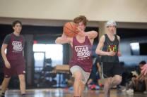 Teens play basketball.