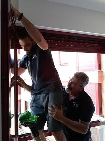 El equipo de El Genio del Aluminio realizando el ajuste de una ventana de aluminio roja