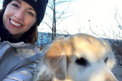Volunteer bike coach, Amy Strom, with her golden retriever Milo.
