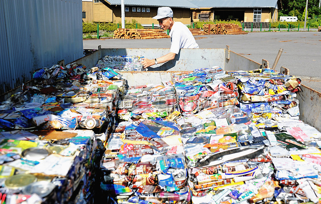 Masaru Goto, 73, stacks up crushed aluminum cans as part of his daily chores at the waste disposal site in central Kamikatsu Town in Shikoku, Japan on July 22, 2008. The town, whose residents number just over 2,000 people, has implemented a waste recycling policy that aims at eliminating waste entirely within the next 12 years and employs retired local residents to care for the waste disposal center. Photographer: Robert Gilhooly