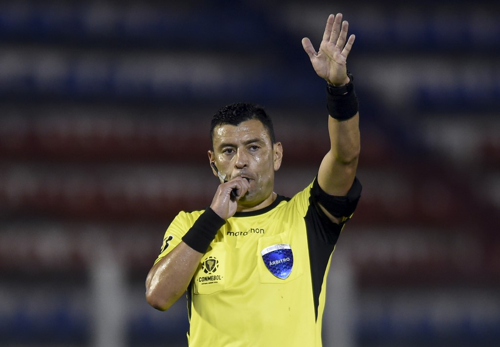 Chilean referee Roberto Tobar blows the whistle as he conducts the closed-door Copa Libertadores group phase football match between Argentina's Tigre and Bolivia's Bolivar at the CA Tigre stadium in Tigre, Argentina, on September 22, 2020, amid the COVID-19 novel coronavirus pandemic. (Photo by Marcelo Endelli / POOL / AFP)