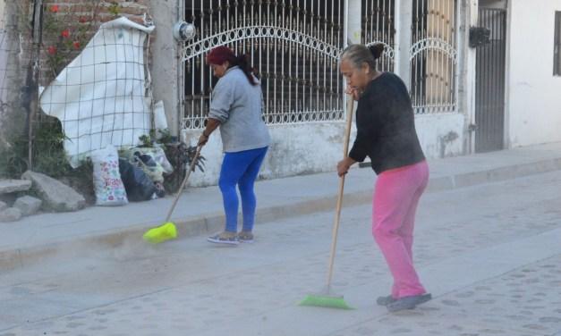 Vecinos limpian el frente de su casa