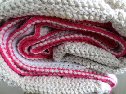 crochet blanket with simple bright pink edge