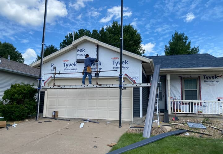 Contractor using ladder jack scaffolding during a vinyl siding install above a garage