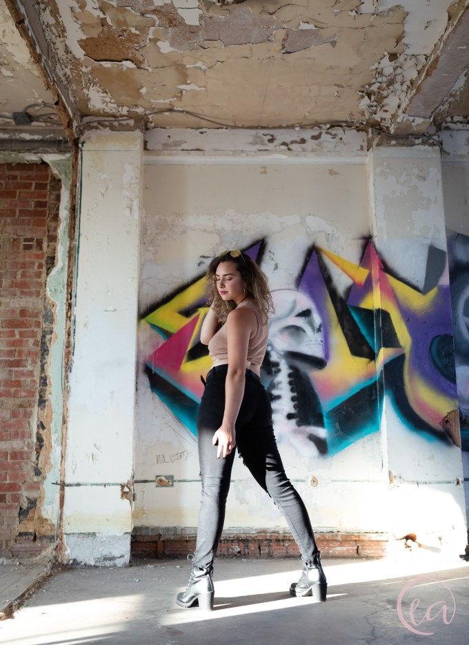 Emily strikes a dramatic pose in the light in front of a bright mural