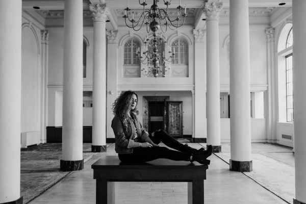 """Emily sits on a table beneath four chandeliers in between tall columns. 90s grunge """"Unpolished Libertine"""" styled shoot"""