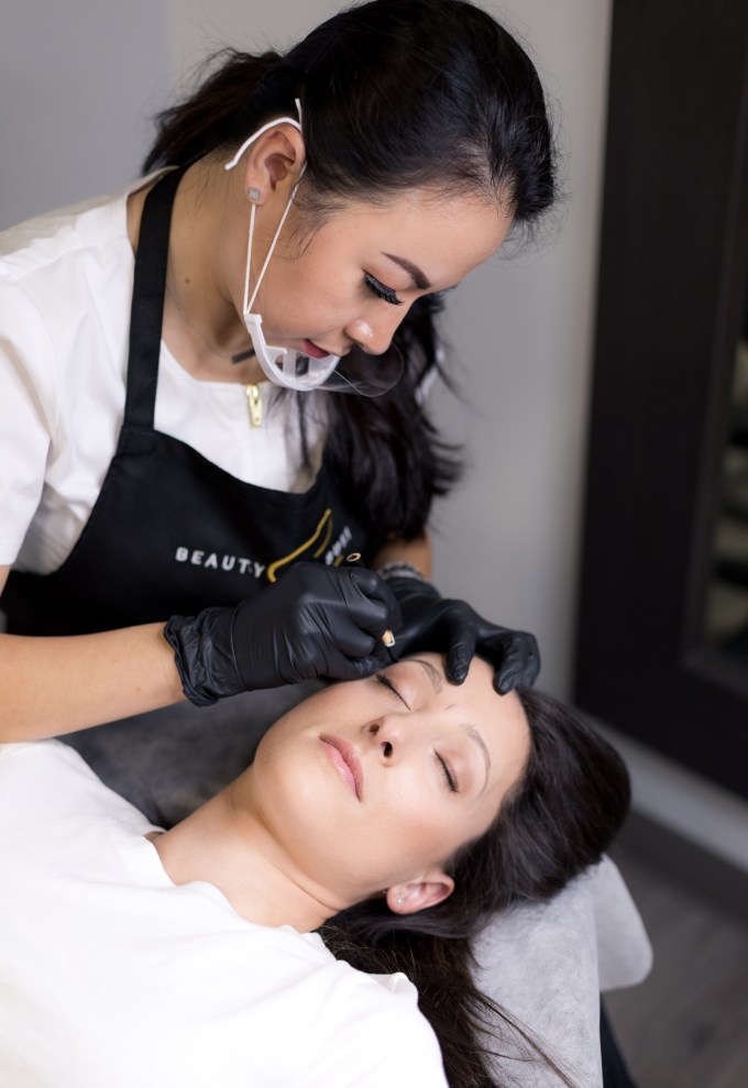 Suki leans over her patient and draws the brow outline.