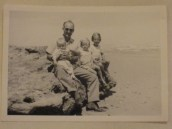 Dad looking young and skittish, holding Richard, me in the middle and Jane on the right, at Victor Harbor in 1961