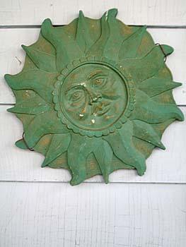Sun sculpture with green patina