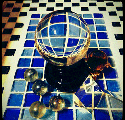 blue and white and black and white tiles are reflected in a clear crystal ball