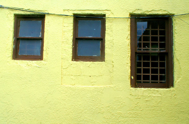 Dark Windows on a yellow stucco wall