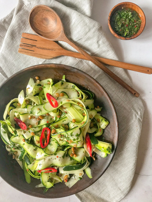 chimichurri courgette salad in a wooden bowl with wooden salad tossers