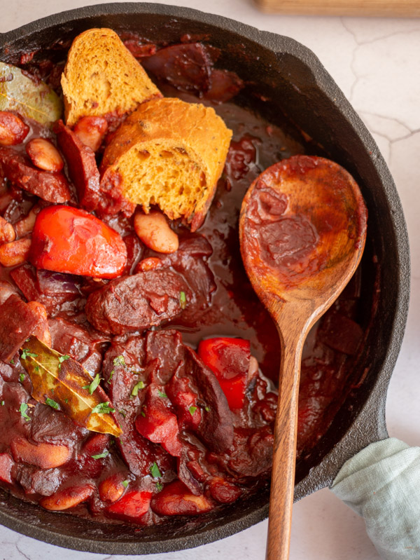 chorizo and butter bean stew in a cast iron frying pan with bread and a spoon