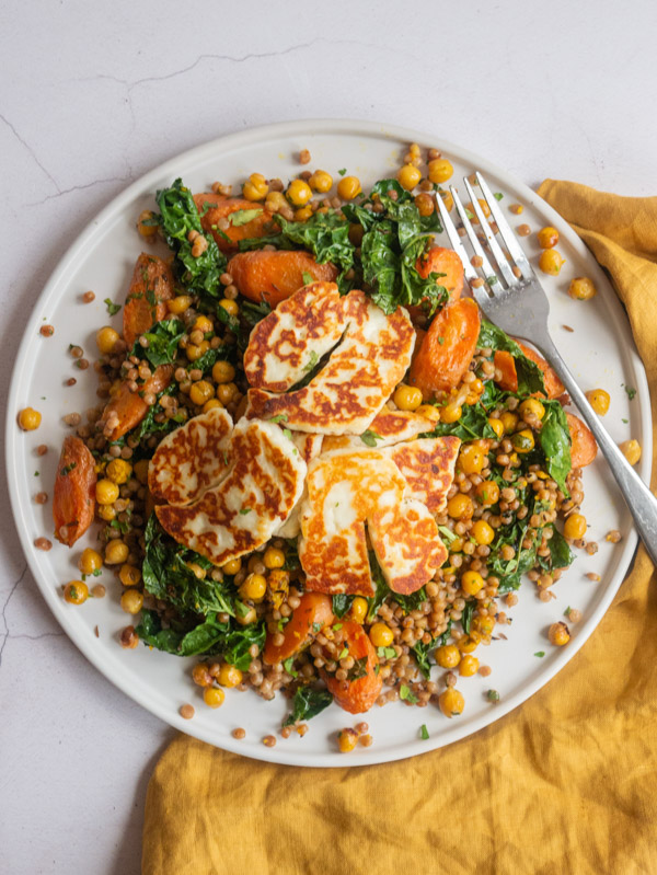 slices of halloumi on top of couscous carrot chickpeas and cavelo nero with a fork
