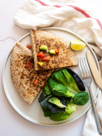 a chorizo and vegetable quesadilla on a plate with salad and a knife and fork