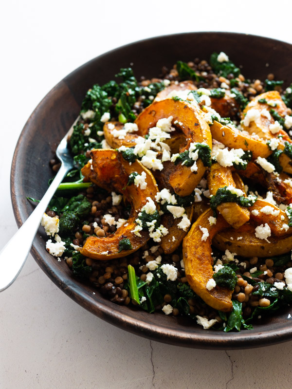 Roast Butternut Squash with Raisin Pesto and Couscous in a wooden bowl with a fork