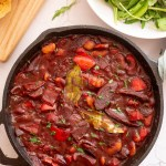 chorizo and butter bean stew in a cast iron frying pan with a bowl of salad and bread