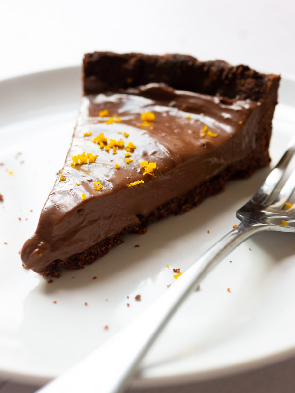 A slice of Vegan Chocolate Orange Tart on a plate with a fork