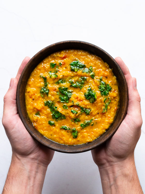 butternut squash tadka dal in a bowl being held by two hands