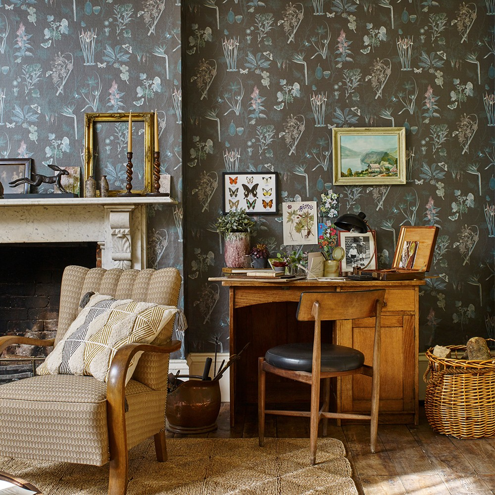 black floral wallpaper in a living room with a botanical theme