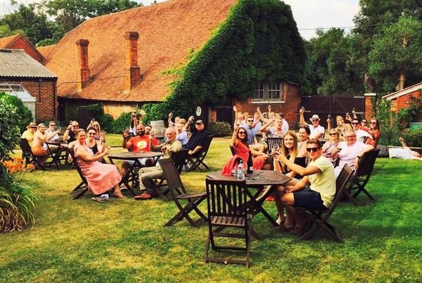 An image of groups of people enjoying a glass of wine in the wine garden of Stanlake Park vineyard in Berkshire