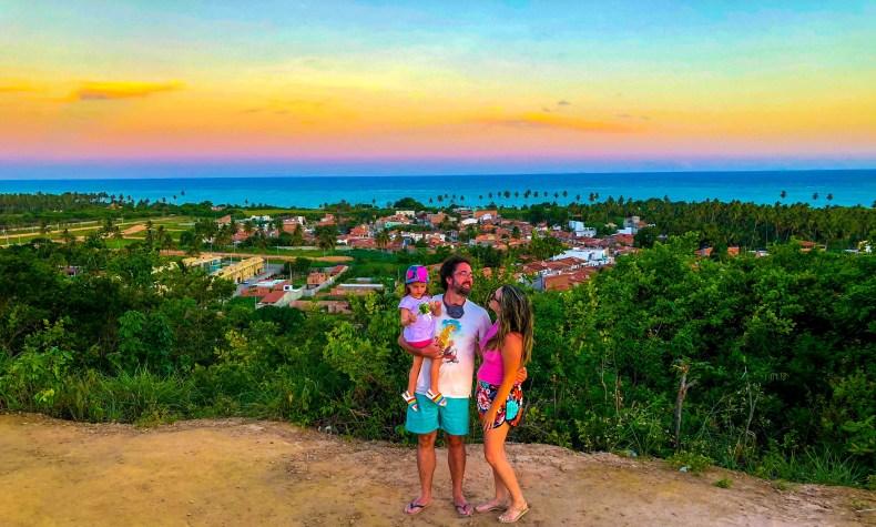 Familia e o por do sol colorido no Mirante Alto de Cruzeiro em São Miguel dos Milagres, Alagoas