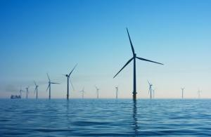 Wind turbines and narrow boats. UK windfarm out at sea.