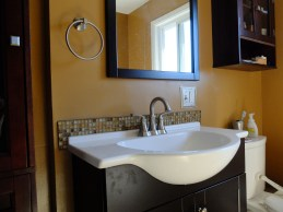 New vanity, faucet, mirror, wall-mount cabinet, linen cabinet, mirror, lighting AND a custom backspalsh!