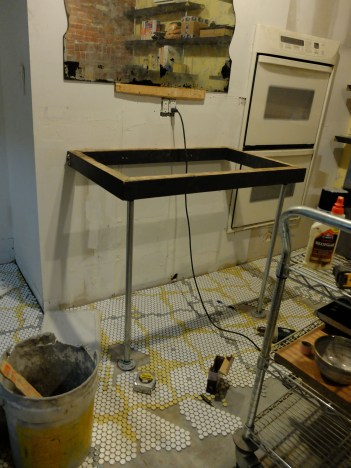 We connected the table to galvanized plumbing pipe - like our floating shelves - and flanged the pipe to the floor.
