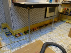 """Our favorite """"trick"""" to eat up unlevel floors - PVC shoe molding from Lowe's. We glue to the bottom and it bends to conform to a floor's slope. We use National Geographic magazines to hold the shoe on - glued with Gorilla Glue (a total mess to use)."""