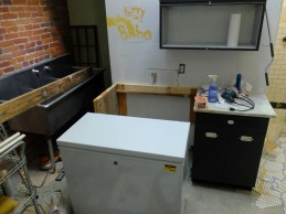 Fitting it all together - a side wall for the console that encloses our chest freezer (new from Home Depot!), along with a custom backsplash that connects the entire console to the sink.