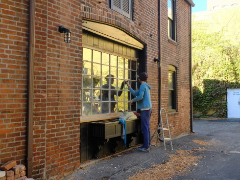 Glazing the panes of glass into the wood frame.