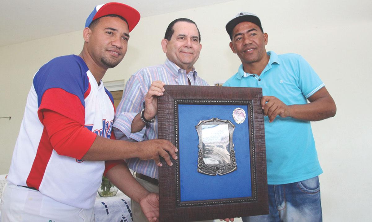 Joel Martínez como directivo del Club San Juan de Ugamba entrega una placa de reconocimiento al senador Amílcar Romero.
