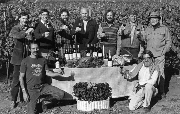 Nine Oregon Winemakers around a table of wines and food in a vineyard in 1980