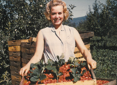 Pat as a teen holding a crate of strawberries on her family's farm in Parkdale, OR