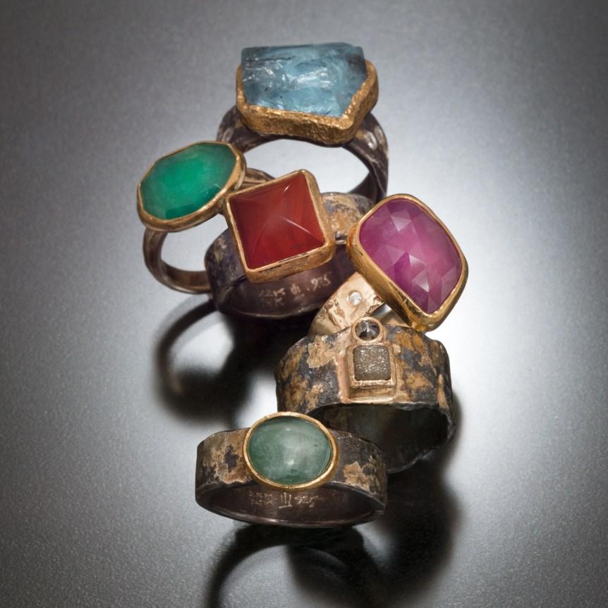 Assorted rings, top to bottom; natural aquamarine crystal formation, emerald, red jasper, pink sapphire, diamond cube, Afgan tourmaline
